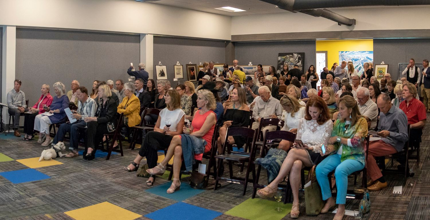 A crowd of people seated at an art auction