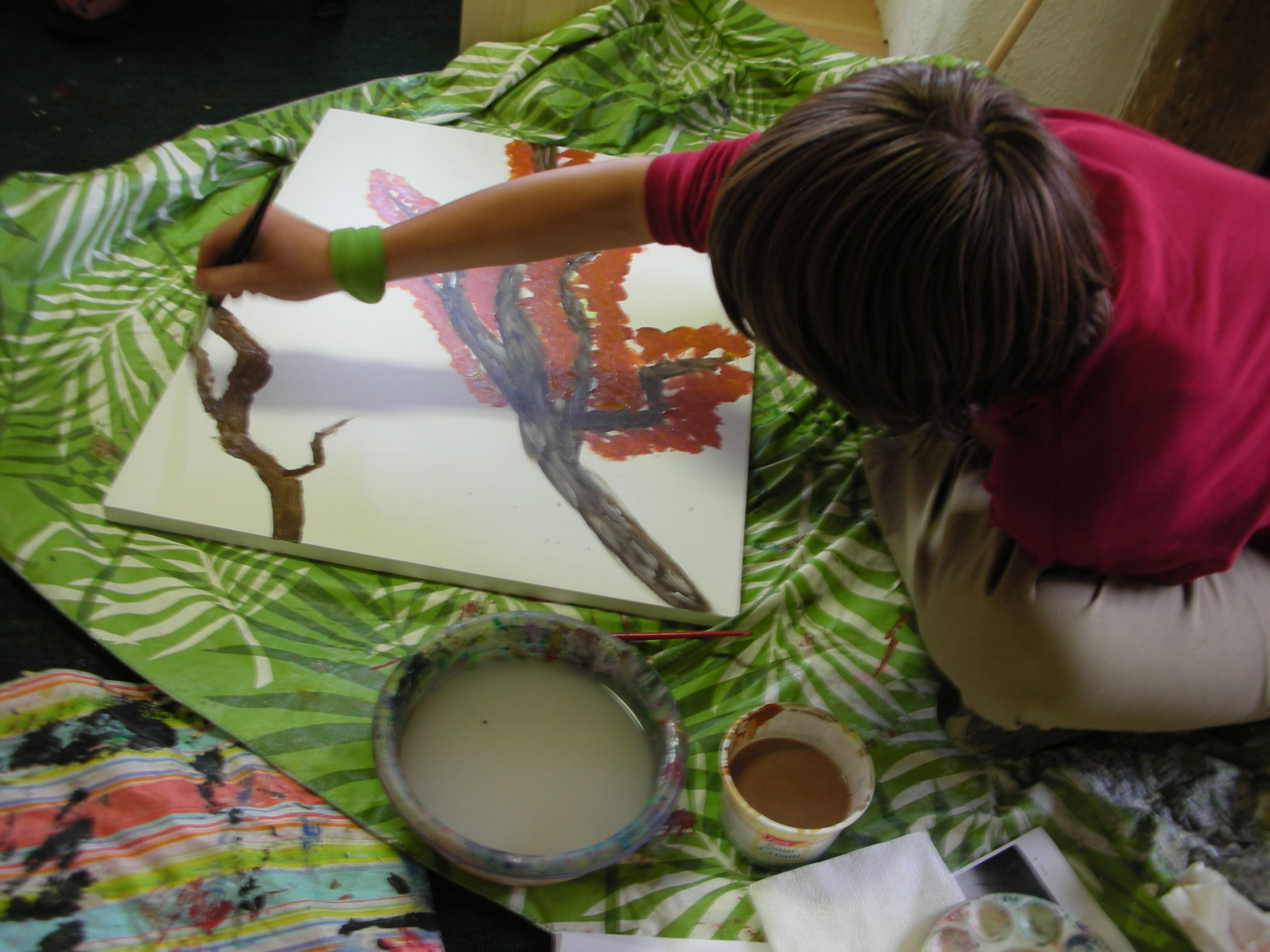 a child painting a picture of a tree
