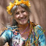 A smiling woman with flowers in her hair