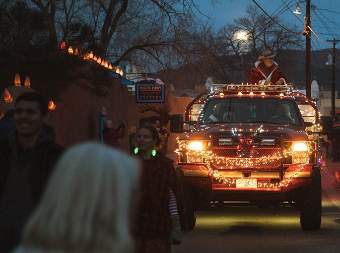 Evening street scene with fire truck covered in Christmas lights